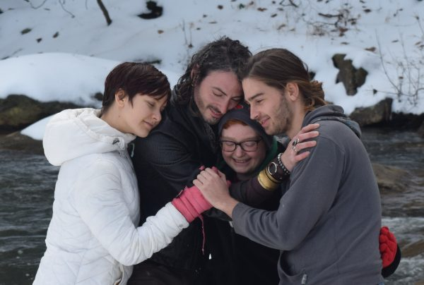 Four people snuggling in the snow